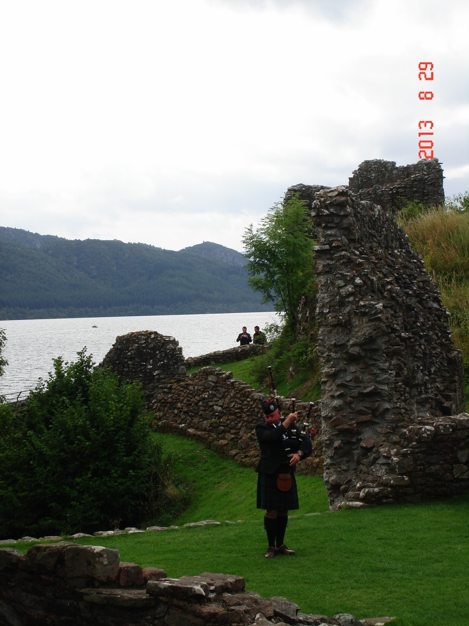 A lone piper greeting visitors to Urqhart Castle, Loch Ness, Scotland.